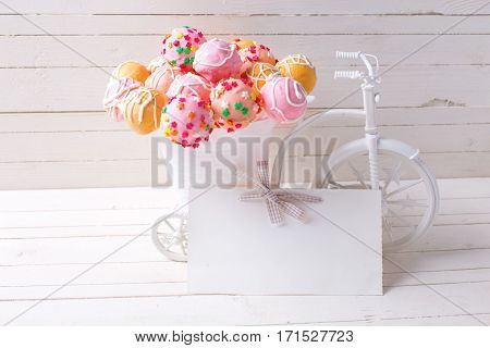 Empty tag and bright cake pops in decorative bicycle on white wooden background. Selective focus. Place for text.