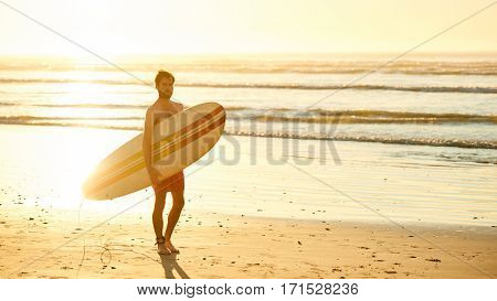 Landscape image of male surfer busy walking on the beach at sunrise while carrying his surfboard under his arm with the ocean waves breaking in the background.