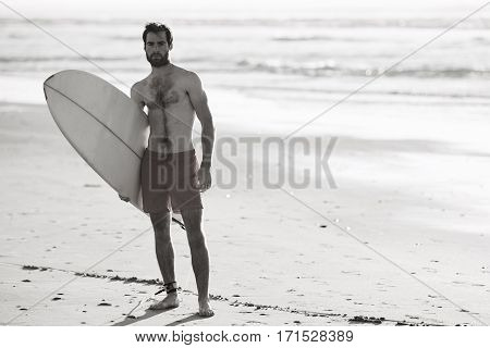 Black and white image of young male surfer standing on beach with his surfboard under his arm and the waves of the ocean behind him in the background.