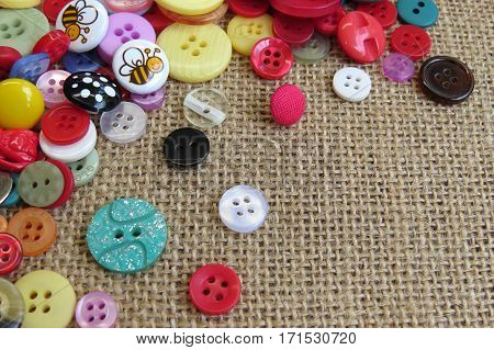 Buttons, lots of buttons. Colourful colorful buttons for sewing and craft on burlap hessian background