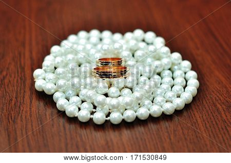 Closeup of wedding rings and white perl