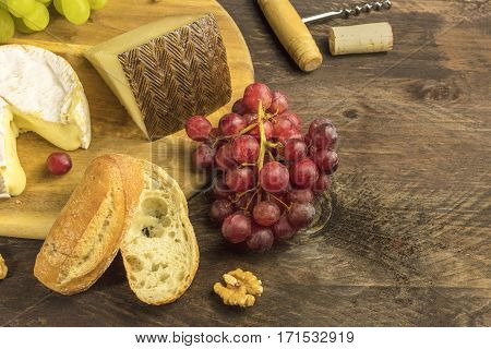 A photo of a wine and cheese tasting, with bread, grapes, corkscrew and cork, with a place for text