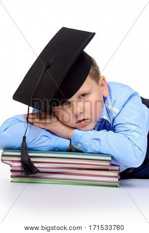 Portrait of a big smart boy in academic hat lying on books. Education. Copy space. Isolated over white background.