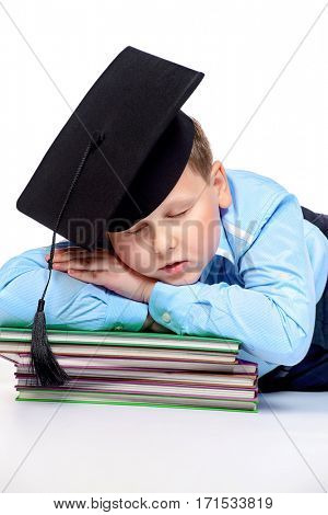 Portrait of a big smart boy in academic hat sleeping on books. Education. Copy space. Isolated over white background.