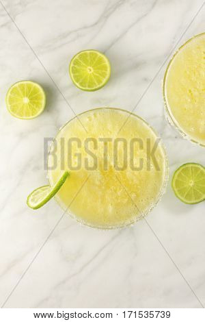 An overhead shot of a lemon Margarita cocktail with a wedge of lime, on a white marble table with copy space