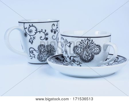 Close up on two white tea cups decorated with designs isolated on white background. Painting on a cup. Side view.