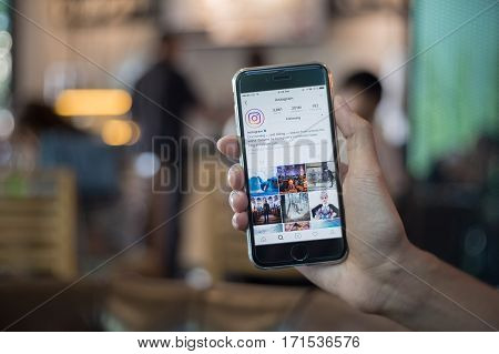 CHIANG MAI THAILAND - DEC 4 2016: A man holds Apple iPhone with Instagram application on the screen. Instagram is a photo-sharing app for smartphones. with coffee shop blurred background