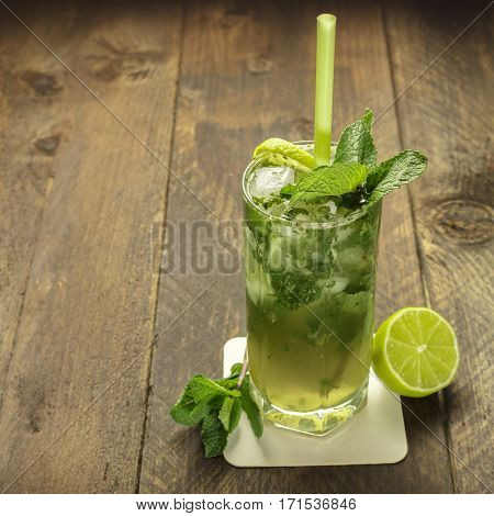 A square photo of a mojito cocktail with mint leaves, a wedge of lime, and a drinking straw, on a dark wooden background with copy space