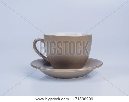 Close up on light brown, ceramic coffee cup standing on a saucer isolated on white background. Side view.