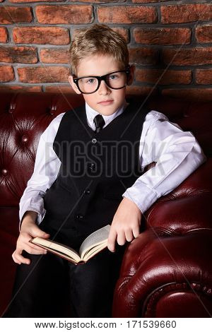 Smart boy in elegant suit and glasses sitting on a Chesterfield sofa with a book. Educational concept. Children's fashion. Vintage style.