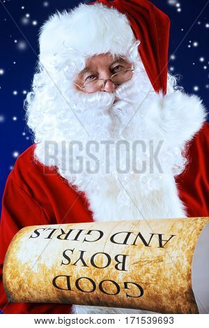 Santa Claus holds an old paper with a list of good boys and girls. Christmas.