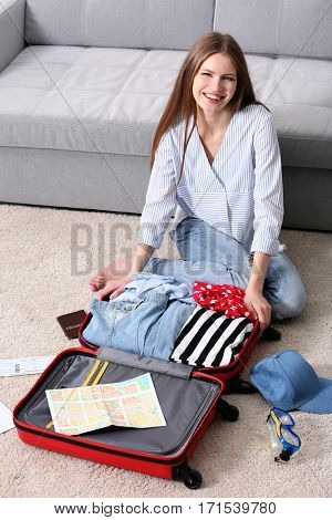 Woman packing her red suitcase in living room