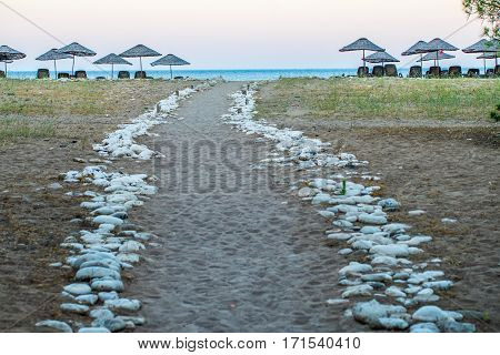 A rock marked road down to beach. There are sunshades and sunbeds and far away small horizontal area sea is visible. Photo is taken in Antalya Turkey