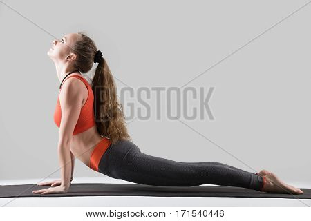 Young attractive woman practicing yoga, stretching in upward facing dog exercise, Urdhva mukha shvanasana pose, working out, wearing sportswear, red tank top, pants, indoor full length, grey studio