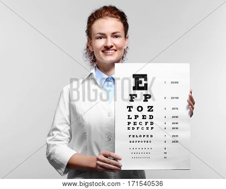 Young doctor holding eyesight test chart on grey background