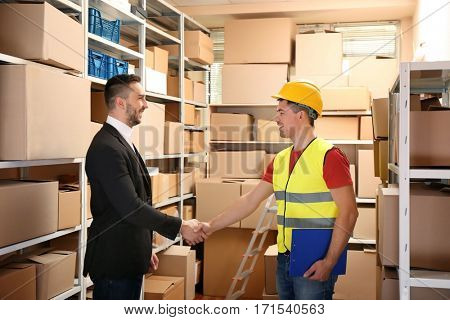 Two businessmen shaking hands at warehouse