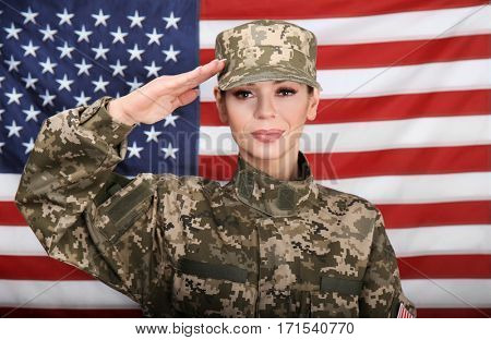 Saluting female soldier with USA flag on background