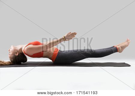 Young happy yogi attractive woman practicing yoga, doing Extended Fish exercise, Matsyasana pose, working out, wearing sportswear, red sports bra, pants, full length, isolated, grey studio background