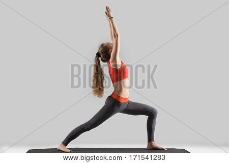 Young attractive yogi woman practicing yoga, standing in Warrior one exercise, Virabhadrasana I pose, working out, wearing sportswear, red sports bra, pants, indoor full length, isolated, grey studio