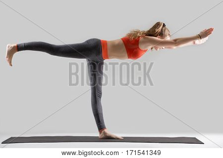 Young attractive woman practicing yoga, standing in Warrior Three exercise, Virabhadrasana III pose, working out, wearing sportswear, red sports bra, pants, indoor full length, isolated, grey studio