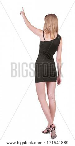 Back view of young blonde woman pointing at wall .beautiful girl in black dress showing gesture. backside view of person. Rear view people collection. Isolated over white background