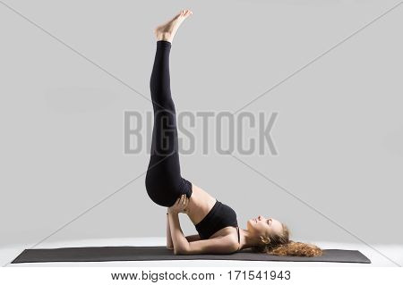 Young happy yogi woman practicing yoga, standing in Viparita Karani exercise, working out, wearing sportswear, black sports bra, pants, indoor full length, isolated against grey studio background