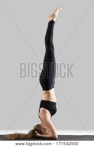 Young attractive yogi woman practicing yoga, standing in headstand exercise, salamba sirsasana pose, working out, wearing sportswear, black sports bra, pants, indoor full length, isolated, grey studio