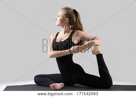 Young happy attractive woman practicing yoga, sitting in One Legged King Pigeon exercise, Eka Pada Rajakapotasana pose, working out, wearing sportswear, black tank top, pants, full length, grey studio