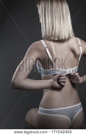 young woman with blue lingerie on gray background