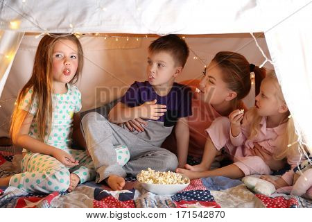 Young woman and cute children eating popcorn in hovel at home