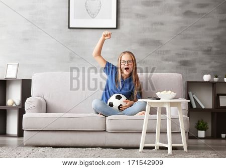 Pretty teenager watching football match on TV at home