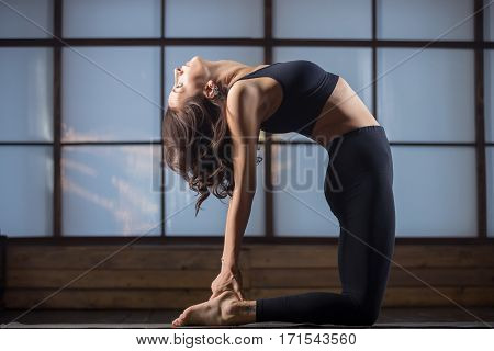 Young attractive woman practicing yoga, standing in Camel exercise, Ustrasana pose, working out, wearing sportswear, black tank top, pants, indoor full length, studio evening practice
