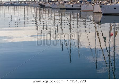 Reflections of masts over sea. Only bottom parts of boats are visible.