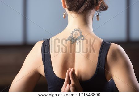 Young attractive woman practicing yoga, making namaste behind the back, working out, wearing sportswear, black tank top, rear view, tattoo on her back, nice earrings, close up. Rear view