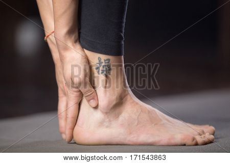 Woman practicing yoga, standing in forward bend exercise, head to knees, uttanasana, pose, working out, studio evening practice, close up, with tattoo on leg meaning Patience in studying