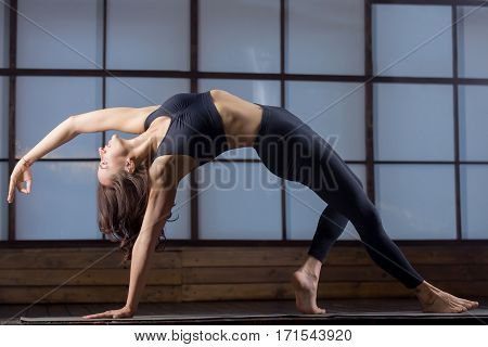 Young woman practicing yoga, doing Wild Thing, Flip-the-Dog pose, Camatkarasana, variation of Bending Side Plank exercise, Vasisthasana, working out, wearing sportswear, black tank top, pants, indoor full length, evening practice
