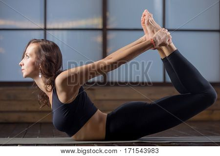 Young attractive woman practicing yoga, stretching in Dhanurasana exercise, Bow pose, working out, wearing sportswear, black tank top, pants, indoor full length, studio evening practice
