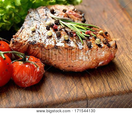 Grilled beef steak with rosemary, salt and pepper on cutting board