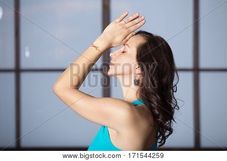 Young attractive woman practicing yoga, making namaste gesture, working out, wearing sportswear, blue tank top, indoor, studio evening practice, profile portrait on meditation session