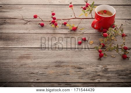 cup of tea with hip roses on wooden table