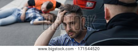 Stressed driver talking with a policeman in the background car accident victim and paramedic panorama