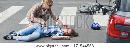 Woman trying to help an unconscious bicyclist lying on a street panorama