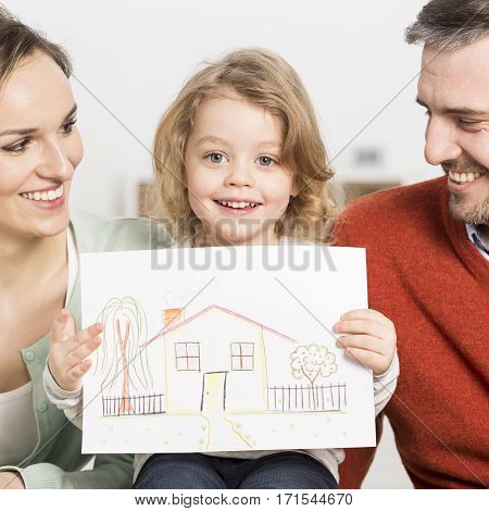 Parents With Kid Holding A Drawing