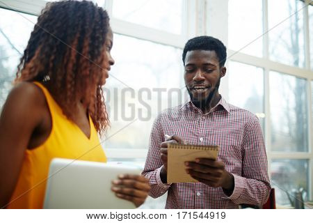 Guy with notepad making notes and talking to colleague
