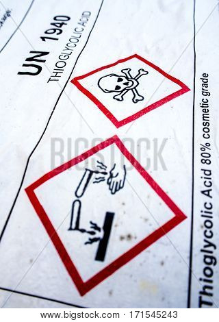 Warning symbol of corrosive material at the acid container