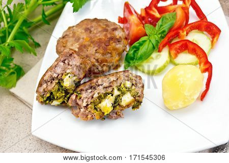 Cutlets stuffed with spinach and egg, slices of tomato, cucumber and pepper, cooked potatoes in a dish on a background of a granite table