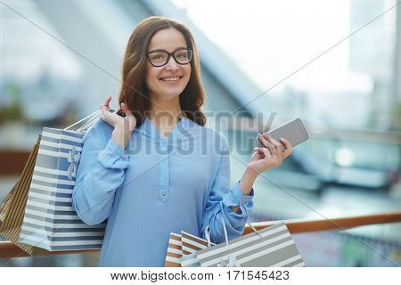 Happy young woman with smartphone and paperbags