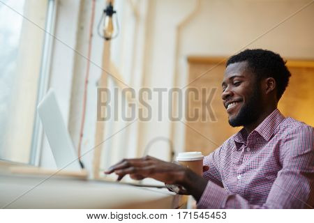 Young designer with drink, browsing in the internet