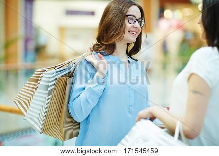 Happy shopper talking to her friend in the mall