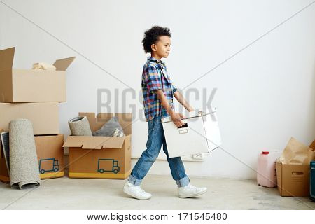Little boy carrying big box during relocation